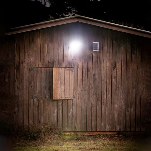 small security light with solar panel mounted outside garden shed