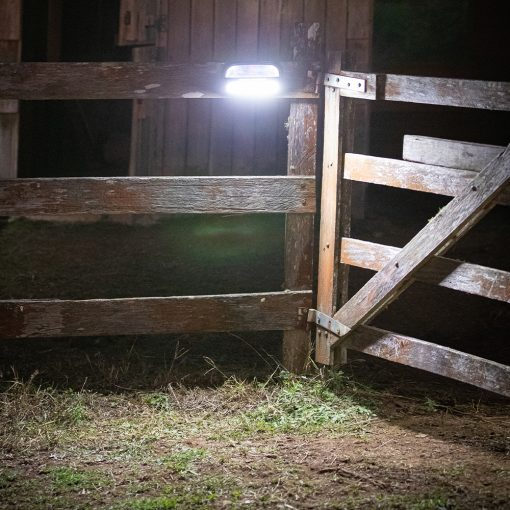 movement detecting outdoor solar fence light shining at night