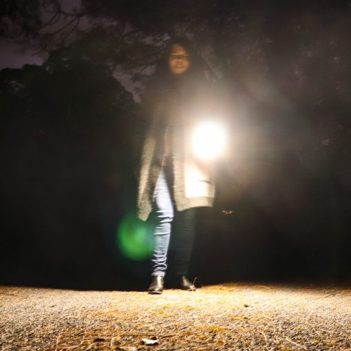woman walking through campsite with portable solar torch