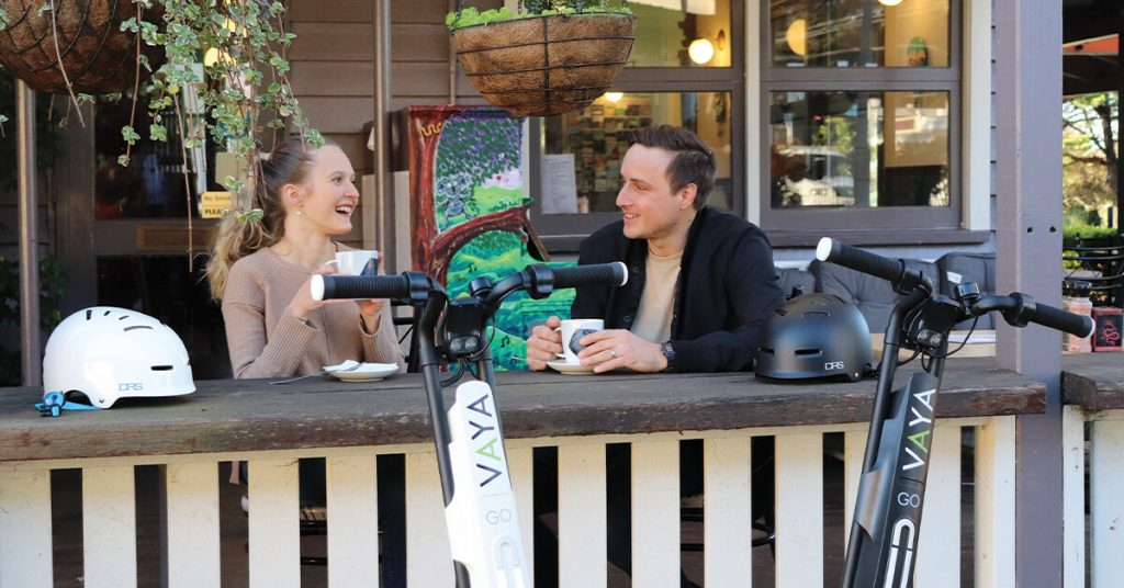 young couple drinking coffee after riding their VAYA Go Electric Scooters around Brisbane