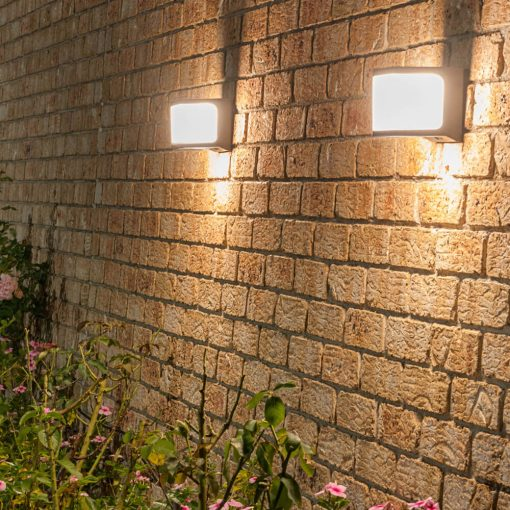 square shaped solar security wall light shining on garden bed full of beautiful flowers